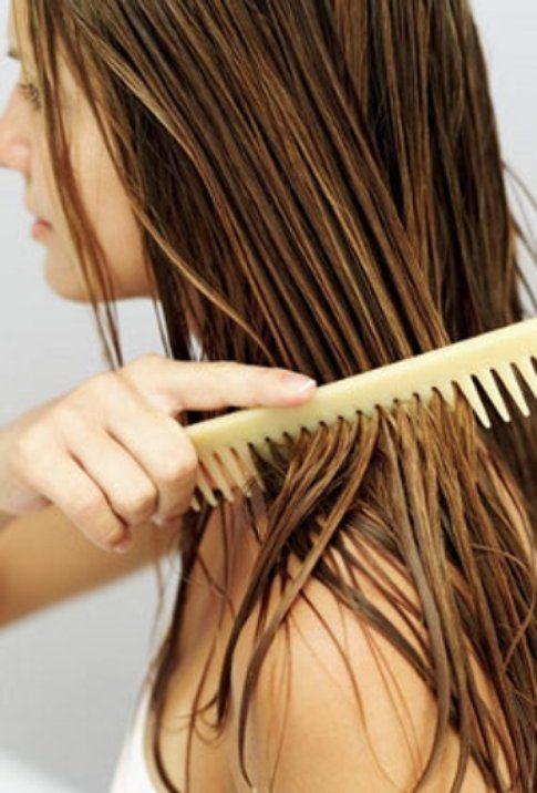 Pettina i capelli con uno strumento di legno a denti larghi