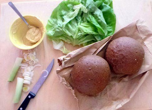 hamburger in preparazione, pane di segale, crema di senape, insalata e cipolotti