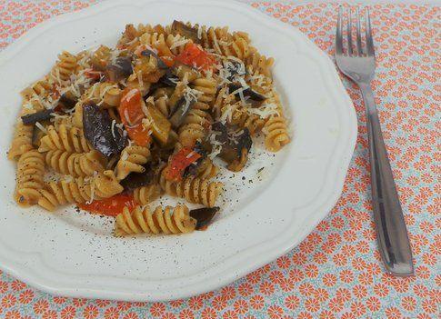 Piatto di pasta integrale bio con melanzane pomodorini e pecorino romano