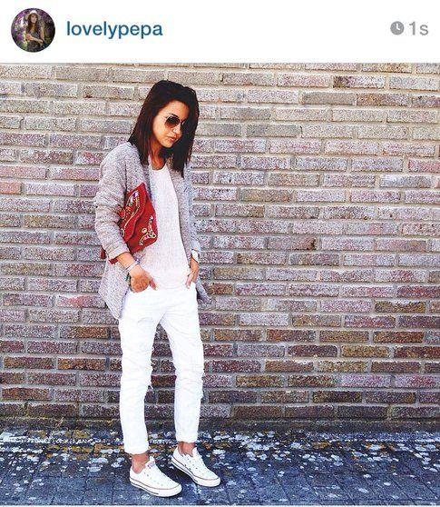 Look di Alexandra: pantaloni e top bianco, clutch rossa e maglioncino beige!