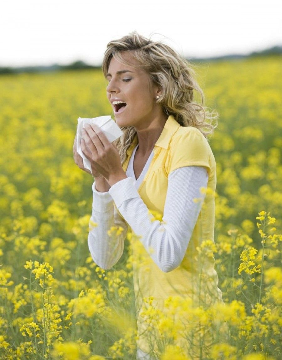 Young woman sneezing in a flowers meadow. Concept: seasonal allergy.