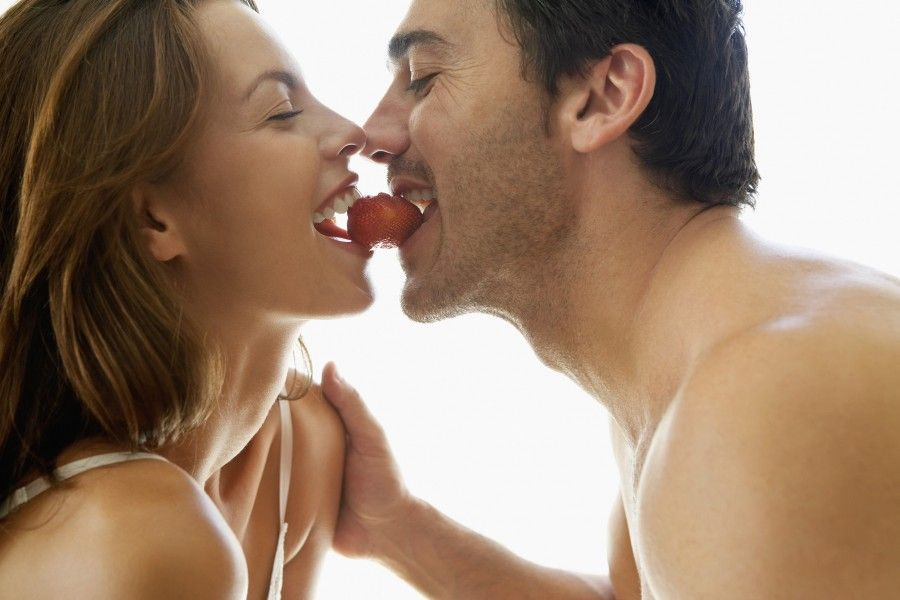 Couple Eating a Strawberry --- Image by © Brooke Fasani Auchincloss/Corbis