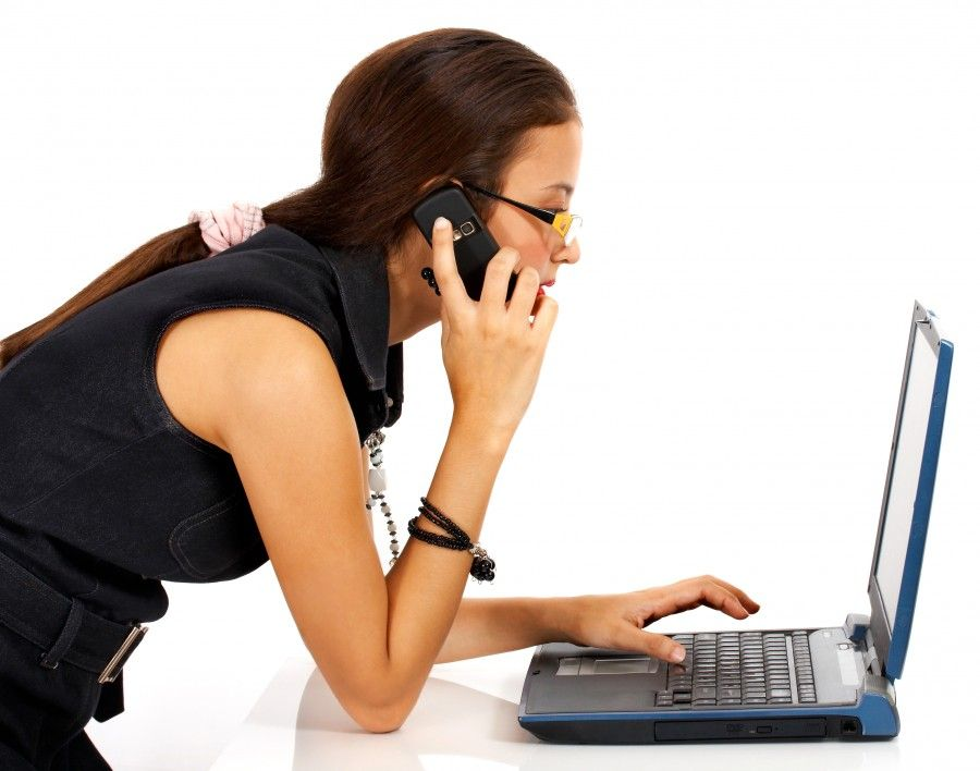 Young Girl Talking On The Telephone And Using A Notebook Computer