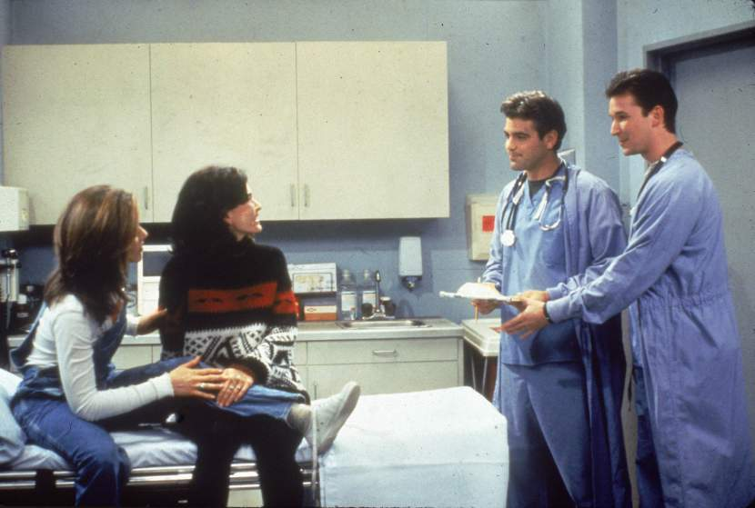 L-R: Jennifer Aniston and Courteney Cox sit in a hospital room, speaking to guest stars George Clooney and Noah Wyle from 'ER' in a still from the television series, 'Friends,' circa 1996. (Photo by Fotos International/Getty Images)