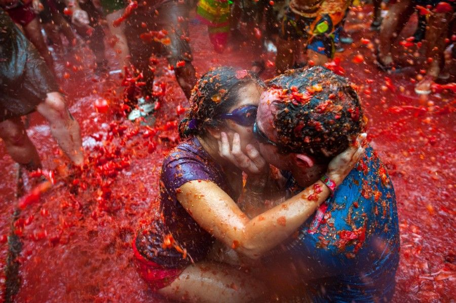 BUNOL, SPAIN - AUGUST 28:  Two Revellers kiss each other covered in tomato pulp while participating the annual Tomatina festival on August 28, 2013 in Bunol, Spain. An estimated 20,000 people threw 130 tons of ripe tomatoes in the world's biggest tomato fight held annually in this Spanish Mediterranean town.  (Photo by David Ramos/Getty Images)