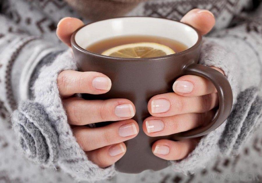 womans-hands-holding-brown-mug-of-tea