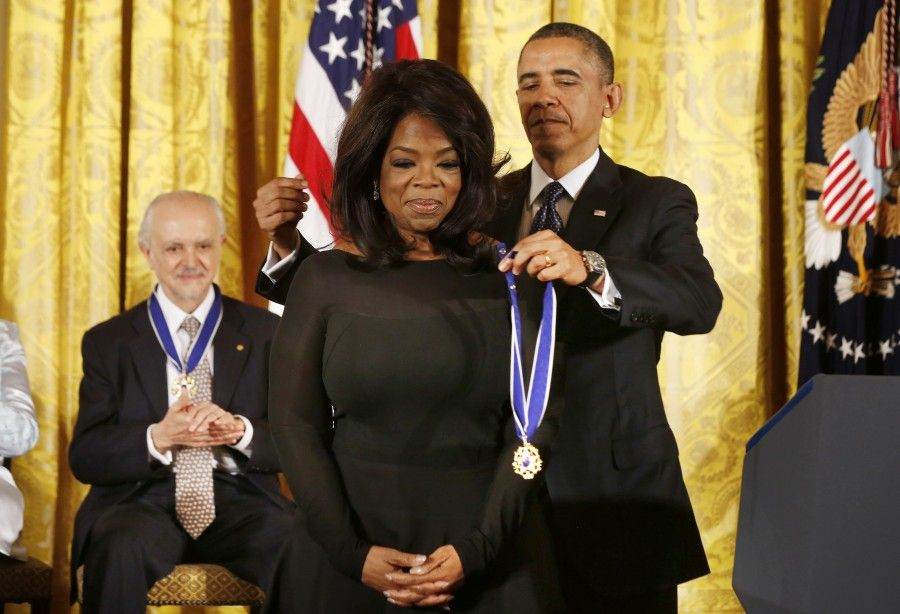 U.S. President Barack Obama presents the Presidential Medal of Freedom to entertainer Oprah Winfrey at a ceremony in the East Room of the White House in Washington, November 20, 2013. REUTERS/Larry Downing (UNITED STATES - Tags: POLITICS ENTERTAINMENT PROFILE TPX IMAGES OF THE DAY)