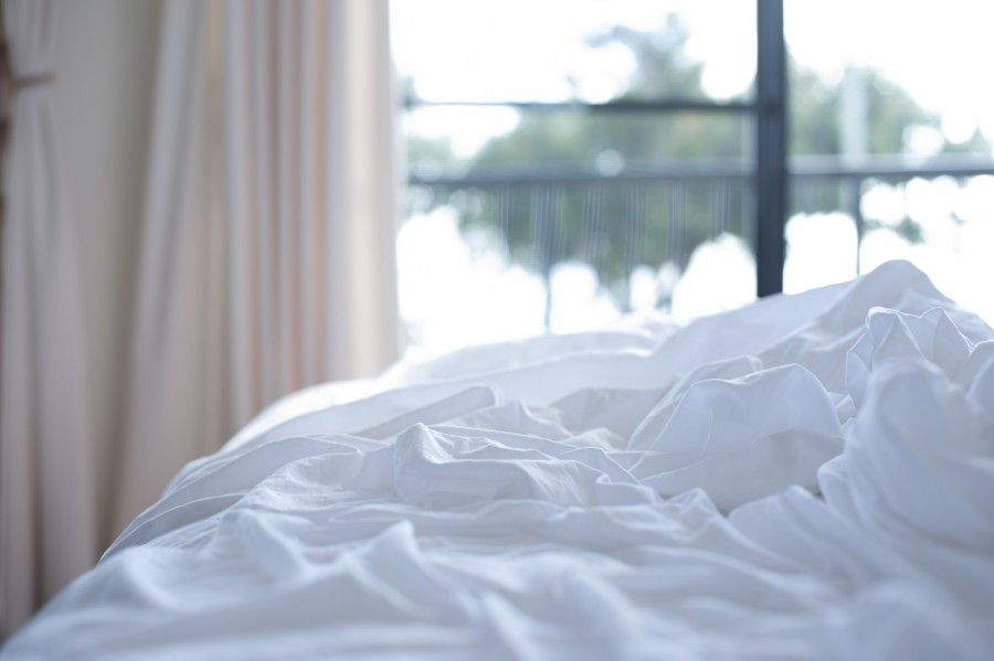 Unmade bed with messed up white bed linen in a rumpled heap and daylight streaming in from the window behind