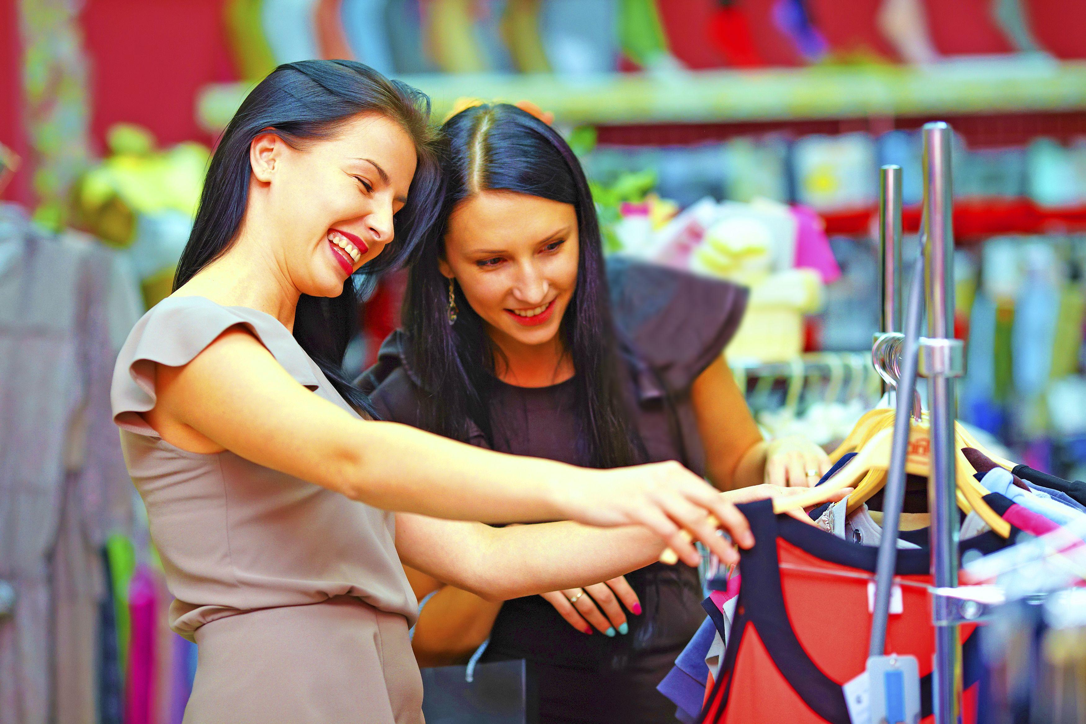 two happy girls buy dress on store sale
