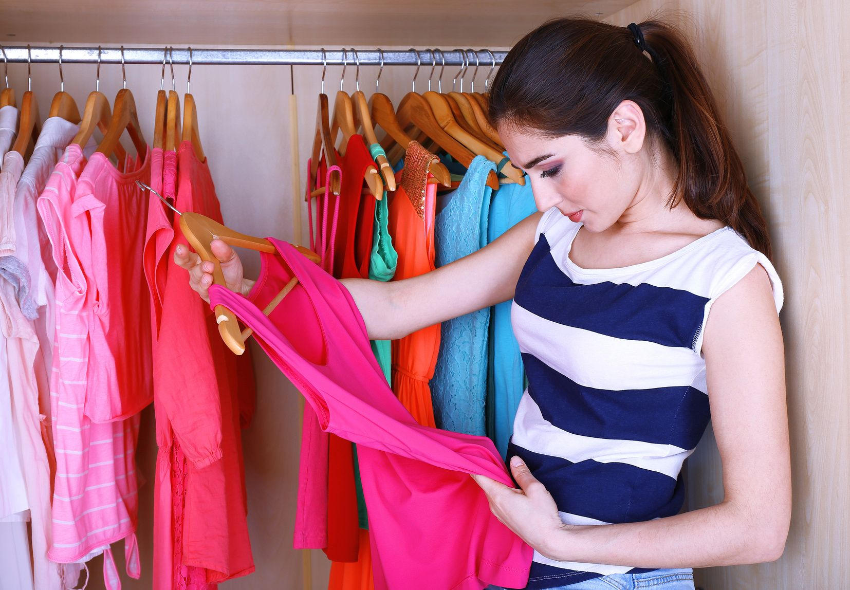 Young woman choose clothes in wardrobe at home