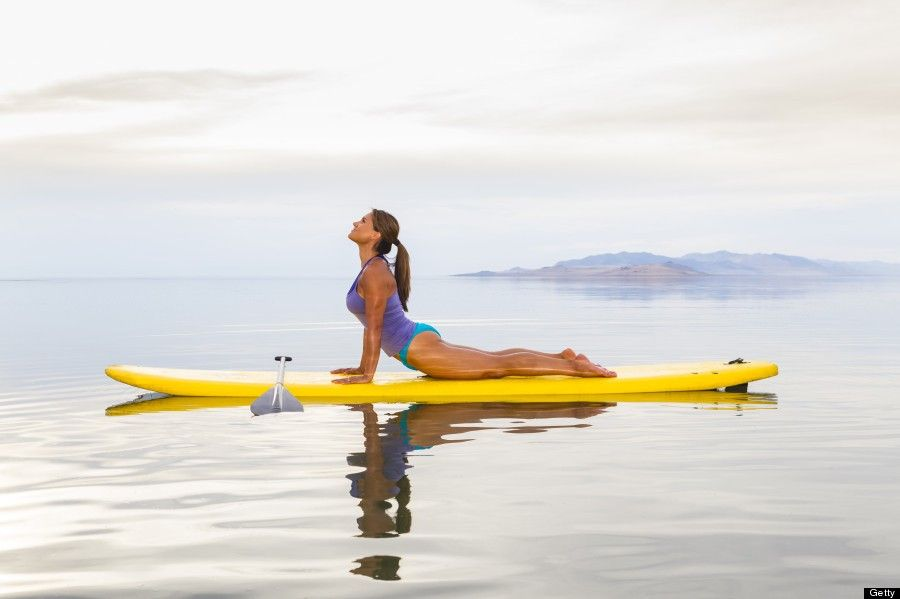 Filipino woman practicing yoga on paddle board