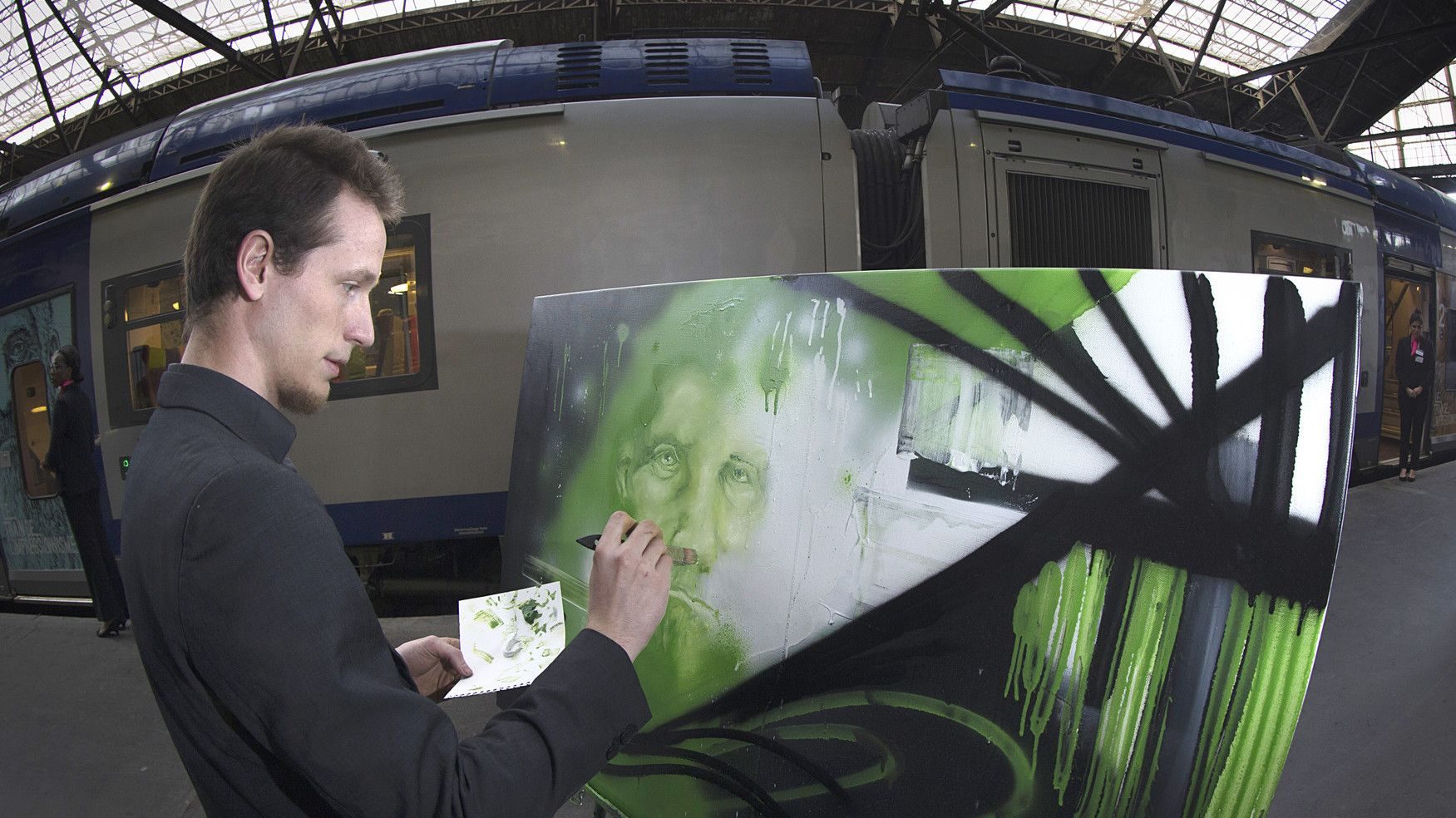 """Rouen artist Bastiste Gateau paints as he stands on the platform of the St Lazare train station in Paris on April 18, 2015,  from where the """"Impressionism Trains"""" will start it journey every weekend until the end of September, linking Paris to Giverny, the home of French Impressionist artist Claude Monet.   AFP PHOTO / JOEL SAGET"""