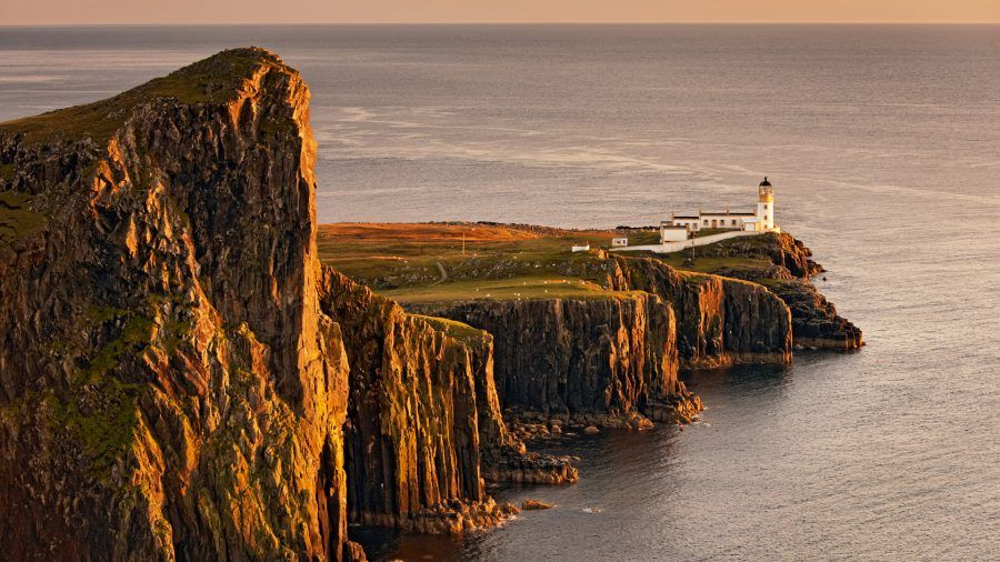 View of sea cliffs and lighthouse at sunset, Neist Point Lighthouse, Isle of Skye, Inner Hebrides, Scotland