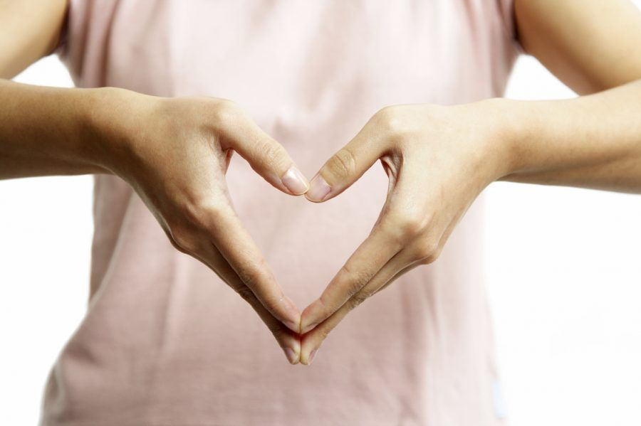 A woman's hands forming a heart symbol