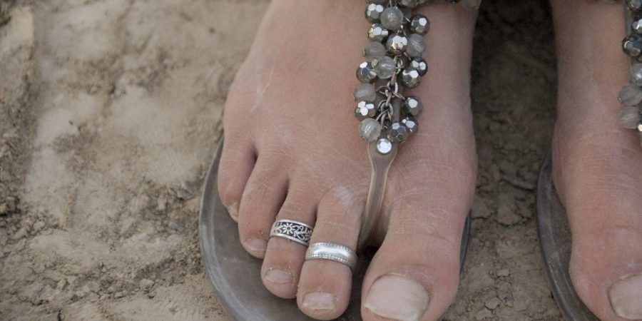 Close up of toe rings and Swarovski crystalbedecked flip flops on a woman's dusty feet on the shore of Lake Issyk Kul, Kyrgyzstan