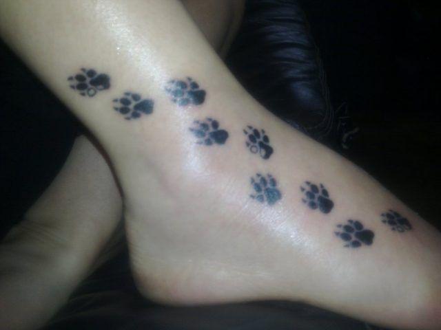 Tatuaggio dedicato ai cani con tante zampette sul piede e sul collo del piede
