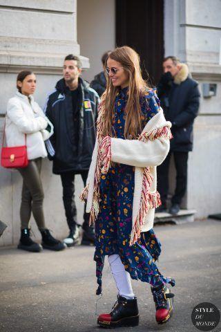 Carlotta Oddi con improbabili stivaletti indossati con calzini tubolari e abbinati ad un abito a stampa e maglione con frange.