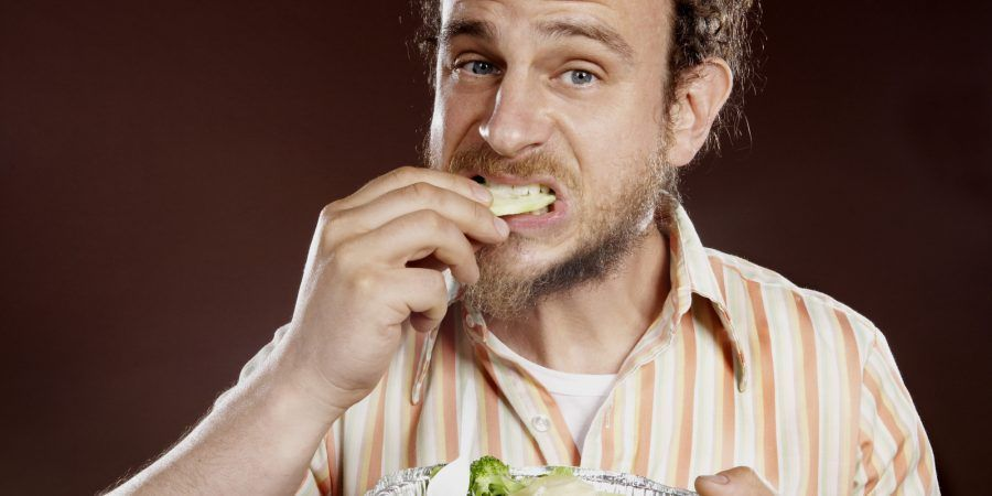 Mature man eating salad, close-up, portrait