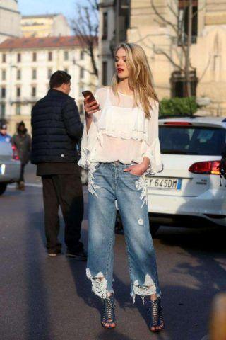 Un look composto da una blusa con ruches di tendenza, un jeans con ricami e sandali con tacco.