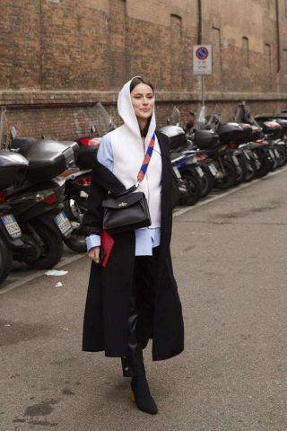 Sovrapposizioni di vari capi di abbigliamento e cappotto indossato in modo asimmetrico.