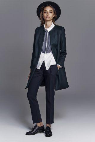 Look tomboy: pantaloni da uomo, gilet, camicia fuori e cappotto, con cappello a falde larghe