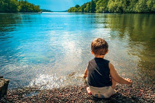 Bambino seduto in riva al lago