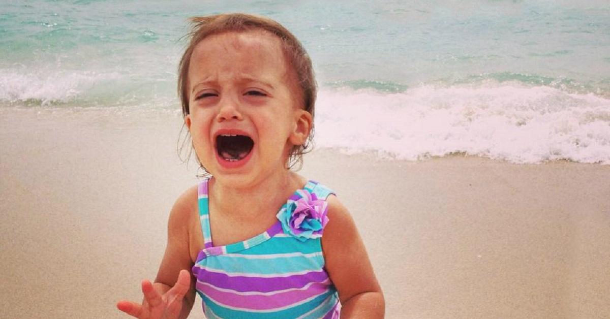 Bambina che piange in spiaggia