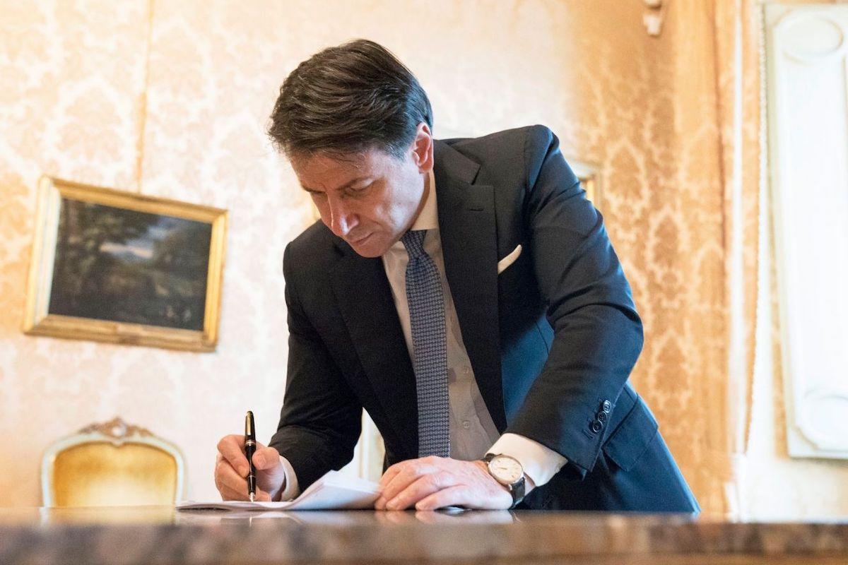 Giuseppe Conte firma il dpcm Covid