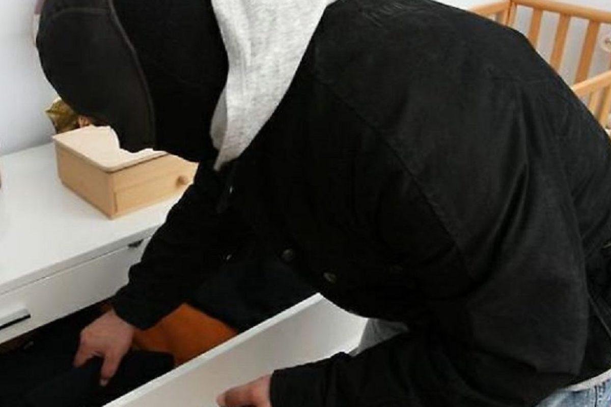 Ladro rovista tra i cassetti di una casa