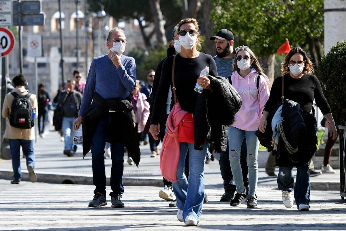 Persone camminano in strada con la mascherina